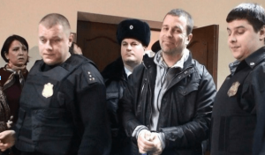 "Russian journalist Serghey Reznik, 40, walks out of court in handcuffs. The photo is posted on his LiveJournal blog via user y_shatalov, who writes that Reznik is ""a fearless journalist who ridiculed our vicious and rotten power until the very last days!"" Credit: Reznik's LiveJournal blog"